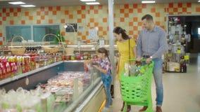Οικογένεια που περπατά μέσω της λεωφόρου με το καροτσάκι αγοράς φιλμ μικρού μήκους