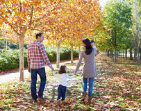 Οικογένεια που περπατά σε ένα πάρκο φθινοπώρου στοκ εικόνες