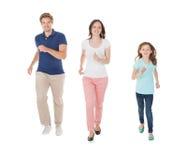 Οικογένεια που περπατά σε μια σειρά πέρα από το άσπρο υπόβαθρο στοκ εικόνες