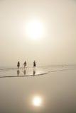 Οικογένεια που περπατά στην όμορφη ομιχλώδη παραλία Στοκ Φωτογραφίες