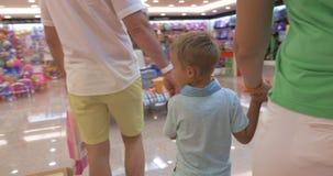 Οικογένεια που περπατά στο κατάστημα παιχνιδιών φιλμ μικρού μήκους