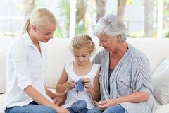 Οικογένεια που πλέκει μαζί στο σπίτι στοκ εικόνες