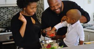 Οικογένεια που προετοιμάζει τα τρόφιμα στην κουζίνα στο σπίτι 4k απόθεμα βίντεο