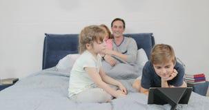 Οικογένεια που προσέχει μαζί το βίντεο στον ψηφιακό υπολογιστή ταμπλετών στα παιδιά κρεβατοκάμαρων με τους γονείς στο κρεβάτι το  απόθεμα βίντεο