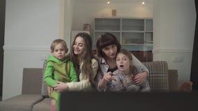 Οικογένεια που προσέχει τη συνεδρίαση TV στον καναπέ στο δωμάτιο φιλοξενουμένων Οι παλαιότερες αδελφές και οι νεώτεροι αμφιθαλείς απόθεμα βίντεο