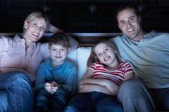Οικογένεια που προσέχει τη TV στον καναπέ από κοινού Στοκ Φωτογραφίες