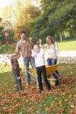 Οικογένεια που ρίχνει τα φύλλα φθινοπώρου στον αέρα Στοκ εικόνα με δικαίωμα ελεύθερης χρήσης