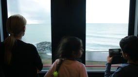 Οικογένεια που ταξιδεύει σε ένα τραίνο και τα βλέμματα μέσω του παραθύρου στη θάλασσα απόθεμα βίντεο