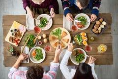 Οικογένεια που τρώει στον πίνακα γευμάτων στοκ εικόνα