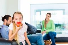 Οικογένεια που τρώει τους νωπούς καρπούς για την υγιή διαβίωση Στοκ Εικόνες