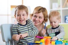 Οικογένεια που φορμάρεται από τα παιχνίδια αργίλου Παιχνίδι μητέρων με τα παιδιά Στοκ Εικόνες