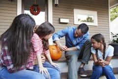 Οικογένεια που χαράζει την κολοκύθα αποκριών στα βήματα σπιτιών στοκ φωτογραφία με δικαίωμα ελεύθερης χρήσης