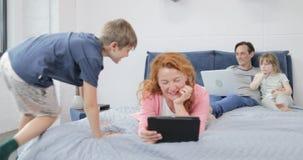 Οικογένεια που χρησιμοποιεί την ταμπλέτα και το φορητό προσωπικό υπολογιστή στους ευτυχείς γονείς κρεβατοκάμαρων που ξοδεύουν το  απόθεμα βίντεο