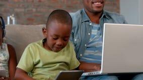 Οικογένεια που χρησιμοποιεί τις συσκευές μέσων στον καναπέ απόθεμα βίντεο