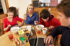 Οικογένεια που χρησιμοποιεί τις συσκευές ταυτόχρονα τρώγοντας το πρόγευμα Στοκ Εικόνες