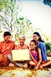 Οικογένεια που χρησιμοποιεί το lap-top στο πάρκο στοκ φωτογραφίες με δικαίωμα ελεύθερης χρήσης