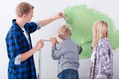 Οικογένεια που χρωματίζει τον εσωτερικό τοίχο του σπιτιού Στοκ φωτογραφία με δικαίωμα ελεύθερης χρήσης