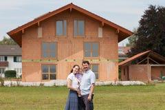 Οικογένεια που χτίζει ένα σπίτι - ακίνητη περιουσία Στοκ φωτογραφία με δικαίωμα ελεύθερης χρήσης