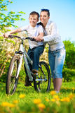 Οικογένεια σε ένα πράσινο πάρκο με ένα ποδήλατο Στοκ φωτογραφίες με δικαίωμα ελεύθερης χρήσης
