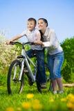 Οικογένεια σε ένα πράσινο πάρκο με ένα ποδήλατο Στοκ Φωτογραφίες