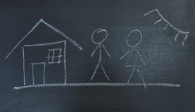 Οικογένεια, σπίτι και ήλιος, χρωματισμένη κιμωλία σε έναν μαύρο πίνακα Στοκ Φωτογραφίες
