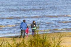 Οικογένεια στην ακτή της παραλίας στο χειμώνα Στοκ εικόνα με δικαίωμα ελεύθερης χρήσης