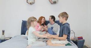 Οικογένεια στην κρεβατοκάμαρα, γονείς που χρησιμοποιεί το έξυπνο τηλέφωνο κυττάρων ενώ τα παιδιά παίζουν τα παιχνίδια μαζί το πρω απόθεμα βίντεο