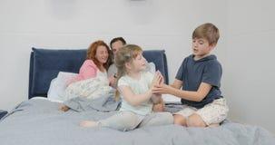 Οικογένεια στην κρεβατοκάμαρα, γονείς που χρησιμοποιεί το έξυπνο τηλέφωνο κυττάρων ενώ τα παιδιά παίζουν μαζί το πρωί απόθεμα βίντεο
