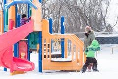 Οικογένεια στην παιδική χαρά στο χιόνι Στοκ εικόνες με δικαίωμα ελεύθερης χρήσης