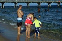 Οικογένεια στην παραλία μπροστά από μια αποβάθρα στο Fort Lauderdale στοκ εικόνες