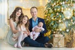 Οικογένεια στη Παραμονή Χριστουγέννων στην εστία Τα παιδιά που ανοίγουν τα Χριστούγεννα παρουσιάζουν Παιδιά κάτω από το χριστουγε στοκ εικόνα