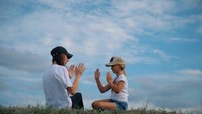 Οικογένεια στη χλόη με τα χέρια επάνω και το όνειρο Ευτυχής οικογενειακή έννοια, τρόπος ζωής, ελευθερία απόθεμα βίντεο