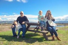 Οικογένεια στον πίνακα πικ-νίκ που απολαμβάνει την ηλιόλουστη ημέρα και την όμορφη θέα Στοκ εικόνα με δικαίωμα ελεύθερης χρήσης