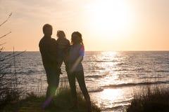 Οικογένεια στο ηλιοβασίλεμα θαλασσίως στοκ φωτογραφίες