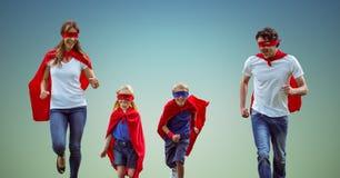 Οικογένεια στο κοστούμι superhero που αντιτίθεται μαζί το μπλε υπόβαθρο ουρανού Στοκ Εικόνα