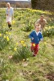 Οικογένεια στο κυνήγι αυγών Πάσχας στο πεδίο Daffodil Στοκ εικόνες με δικαίωμα ελεύθερης χρήσης
