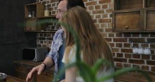 Οικογένεια στο μαγειρεύοντας γεύμα πατέρων και κορών κουζινών ενώ μητέρα με το γιο που κάνει σερφ Διαδίκτυο που χρησιμοποιεί τον  απόθεμα βίντεο