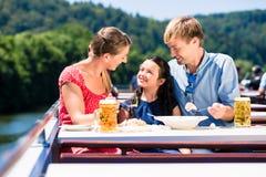 Οικογένεια στο μεσημεριανό γεύμα στην κρουαζιέρα ποταμών με τα γυαλιά μπύρας στη γέφυρα Στοκ εικόνα με δικαίωμα ελεύθερης χρήσης
