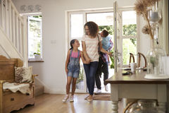 Οικογένεια στο σπίτι επιστροφής διαδρόμων από κοινού στοκ εικόνες