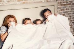 Οικογένεια στο σπίτι κάτω από το coverlet Στοκ φωτογραφία με δικαίωμα ελεύθερης χρήσης