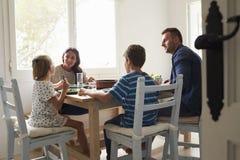 Οικογένεια στο σπίτι να φάει το γεύμα από κοινού Στοκ Φωτογραφίες