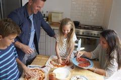 Οικογένεια στο σπίτι στην κουζίνα που κατασκευάζει τις πίτσες από κοινού Στοκ Εικόνα