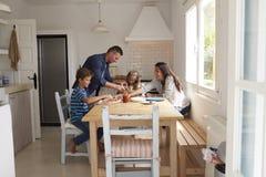 Οικογένεια στο σπίτι στην κουζίνα που κατασκευάζει τις πίτσες από κοινού Στοκ Εικόνες
