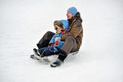 Οικογένεια της μητέρας και του παιδιού που κυλούν το έλκηθρο στοκ εικόνα με δικαίωμα ελεύθερης χρήσης