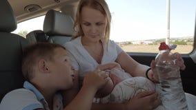 Οικογένεια της μητέρας, του παλαιότερων γιου και του μωρού στο αυτοκίνητο απόθεμα βίντεο