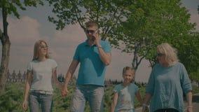 Οικογένεια τριών γενεάς που παίρνει έναν περίπατο στο θερινό πάρκο απόθεμα βίντεο