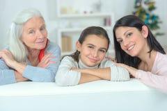 Οικογένεια τριών γενεών που στηρίζεται στον καναπέ στοκ φωτογραφία