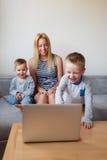 Οικογένεια τριών χρησιμοποιώντας την τηλεοπτική κάμερα κλήσης lap-top Στοκ φωτογραφία με δικαίωμα ελεύθερης χρήσης