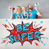 Οικογένεια των superheroes που κρατούν το έμβλημα στοκ εικόνα με δικαίωμα ελεύθερης χρήσης