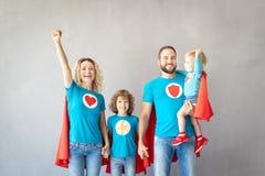 Οικογένεια των superheroes που παίζουν στο σπίτι στοκ εικόνα